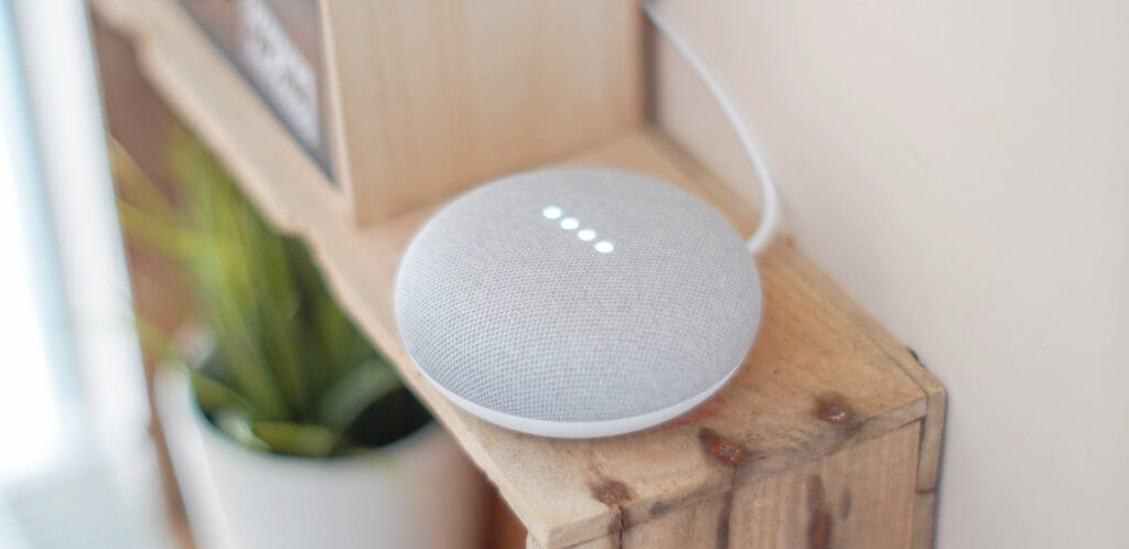 White Google Home Mini Placed On A Wooden Showcase